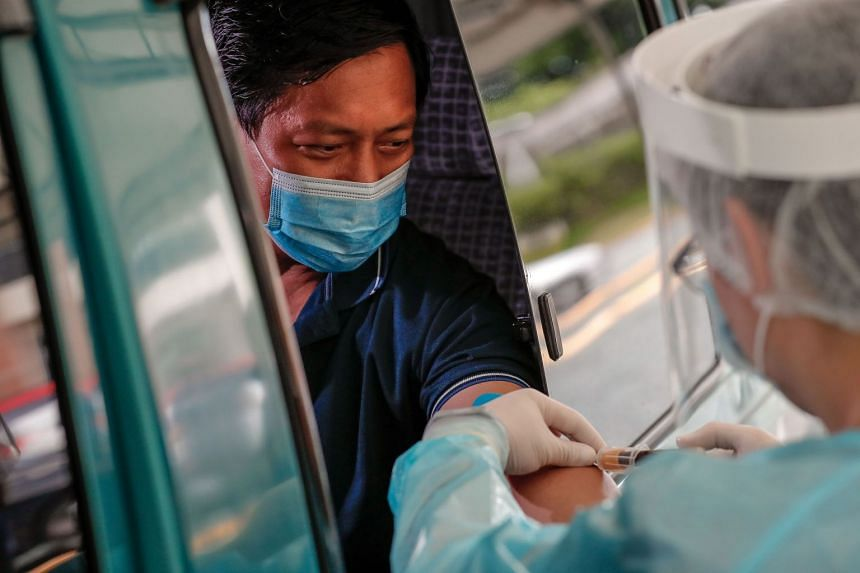 A health worker performs an antibody test at a drive-thru Covid-19 testing facility in the Philippines, July 7, 2020..