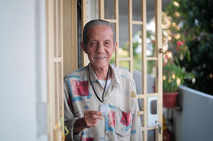 Mr Ng Cheong Hwee, 82, with his TraceTogether token, which he wears around his neck whenever he goes out. Mr Ng does not own a smartphone. He had never heard of TraceTogether either, as he does not keep up with the news. Volunteers and staff with the