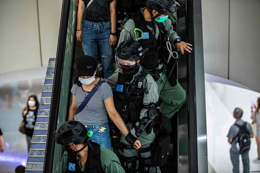 Police take away a woman during a demonstration in a mall in Hong Kong, on July 6, 2020.