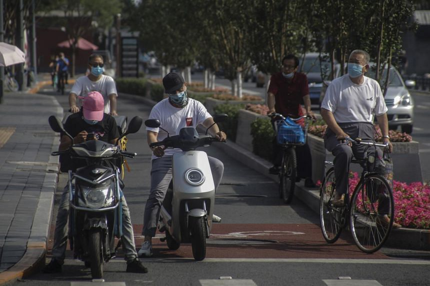 People wearing face masks ride scooters and bicycles in Beijing on July 6, 2020.