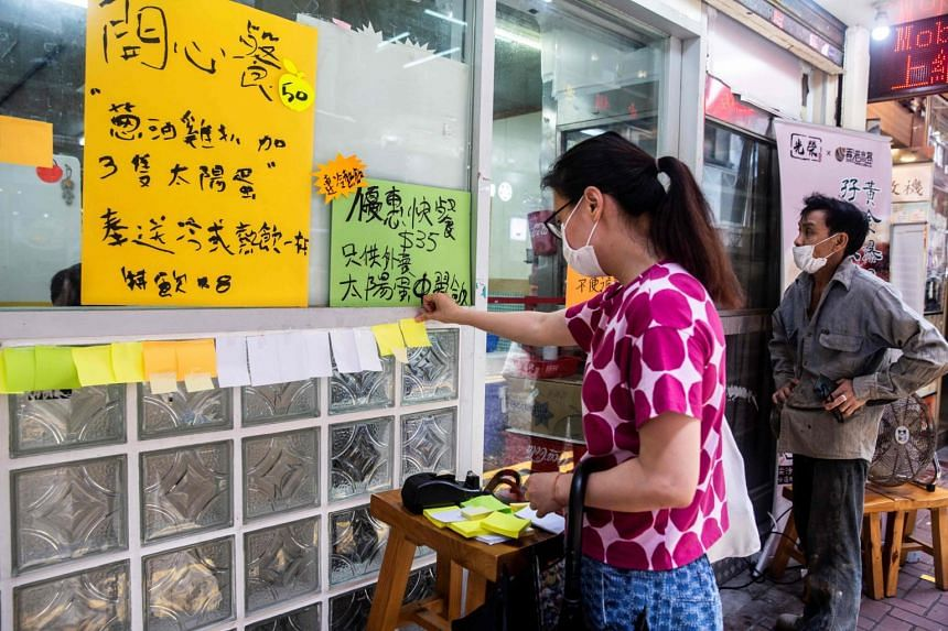 A woman sticks a blank note onto a Lennon Wall outside a pro-democracy restaurant in Hong Kong on July 3, 2020.