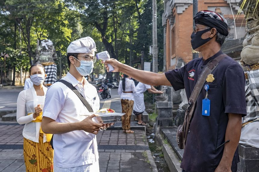 A Balinese security guard taking the temperature of a temple visitor last Friday. Pressure is mounting on the authorities to rescue the battered tourism industry in Bali.