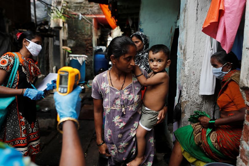 A healthcare worker checking the temperature of residents of a slum area during a check-up campaign for Covid-19 in Mumbai yesterday. India has failed to suppress new cases despite implementing one of the world's most expansive lockdowns at the end o