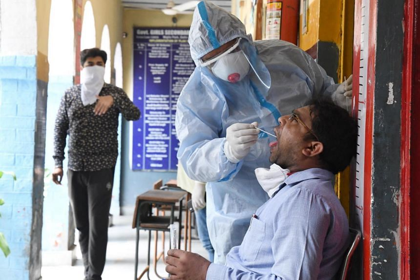 A medical lab technician collects swab samples for coronavirus detection testing in New Delhi on June 23, 2020.