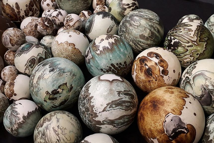 Ceramic artist Steven Low (above) has created a set of clay globes (left) in the style of his Planet series. The colourful spheres resemble miniature Earths.