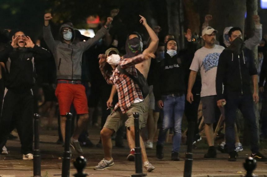 Protesters throw projectiles at police in front of the Serbian Parliament building in Belgrade, Serbia, on July 7, 2020.