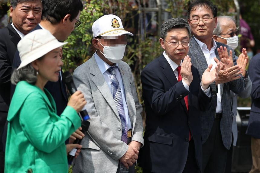 The two men - one surnamed Han (second from left) and the other Ro - say they were captured during the 1950-53 Korean War.