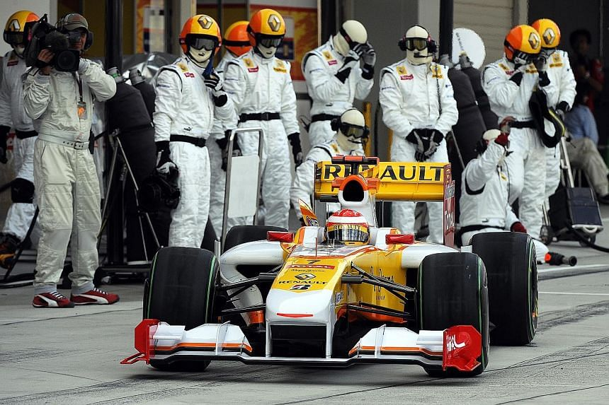Spanish driver Fernando Alonso (above) in his Renault during a pit stop in the qualifying session of the Japanese Grand Prix in 2009. He will be back with the French team next season, partnering Frenchman Esteban Ocon, but the length of his contract