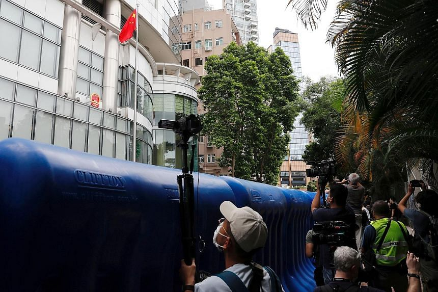 Journalists filming the opening ceremony from behind water barriers. The office is temporarily located at Metropark Hotel in Causeway Bay. (From left) Mr Luo Huining, chief of Beijing's liaison office in Hong Kong, Chief Executive Carrie Lam, former