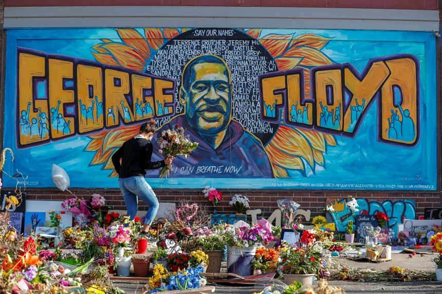 A woman holds a bouquet at the site of the arrest of George Floyd, who died while in police custody, in Minneapolis, on June 14, 2020.