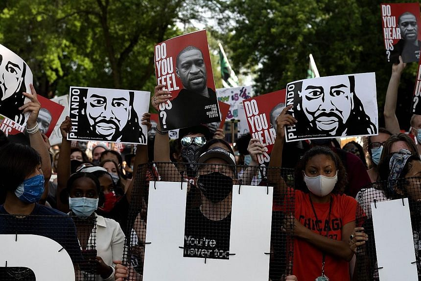 Demonstrators with banners bearing the likenesses of Mr Philando Castile and Mr George Floyd during a protest march in Minnesota on Monday, the fourth-year anniversary of Mr Castile's death. The African American was shot and killed during a traffic s