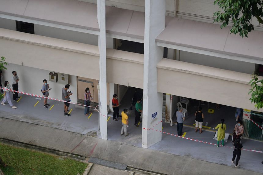 Voters wait in line to cast their ballots at a polling station in Clementi Street 13, on July 10, 2020.
