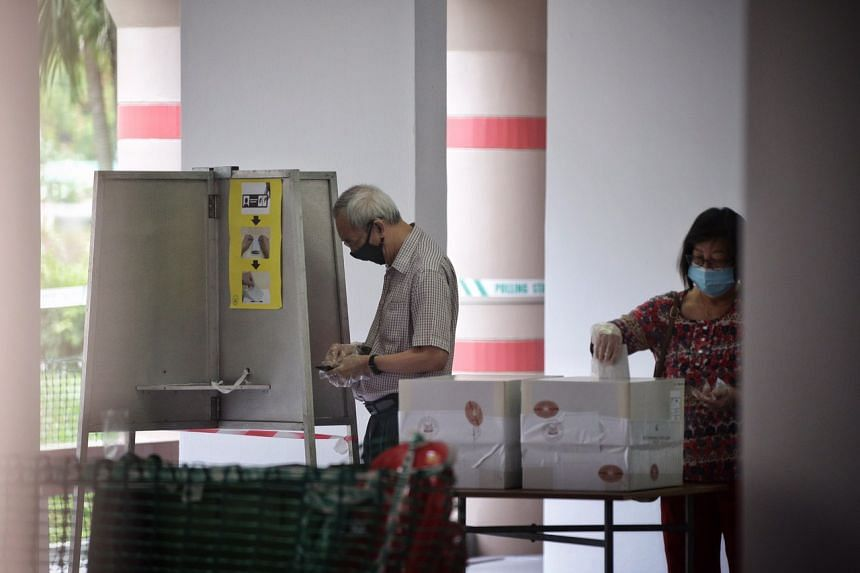 Voters don masks and gloves while casting their votes at 536 Pasir Ris Drive 1, on July 10, 2020.