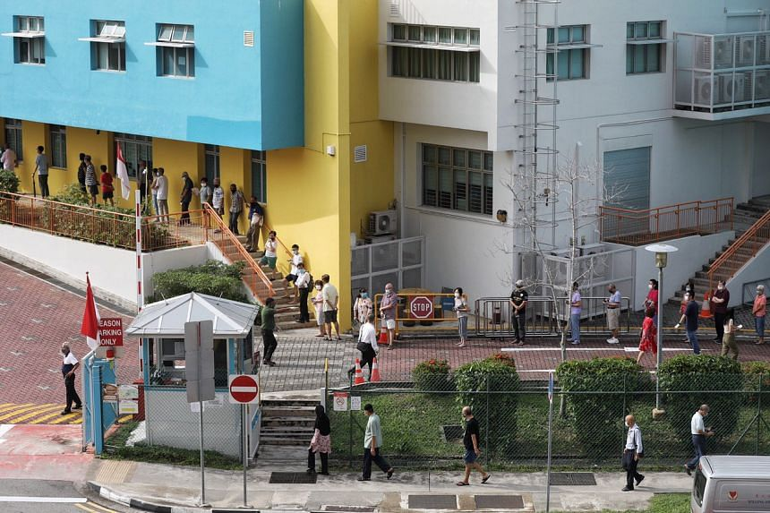 Voters wait in line to enter Changkat Primary School Polling Station, on July 10, 2020.