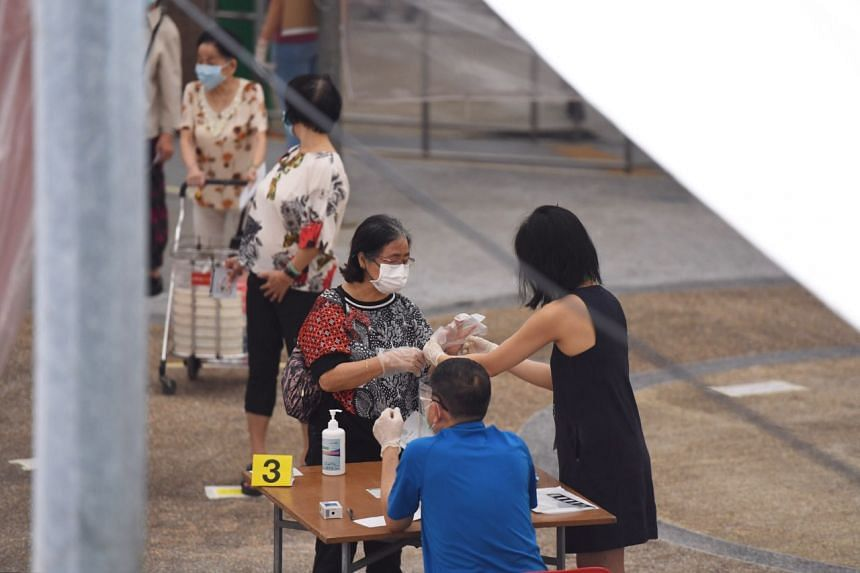Voters at Block 107 Towner Road using the hand sanitisers and gloves provided for voting on July 10, 2020.