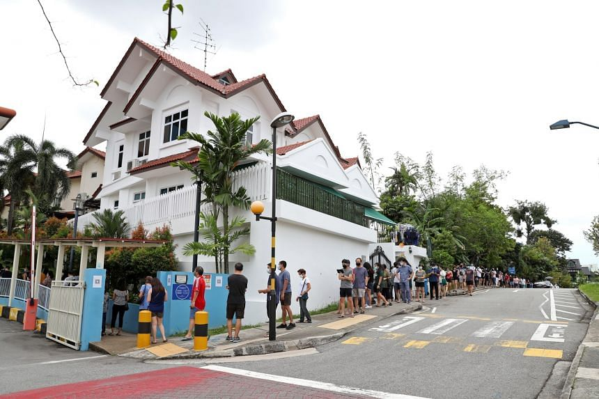 Residents queue along Burghley Drive to cast votes at CHIJ Our Lady of Good Counsel on July 10, 2020.