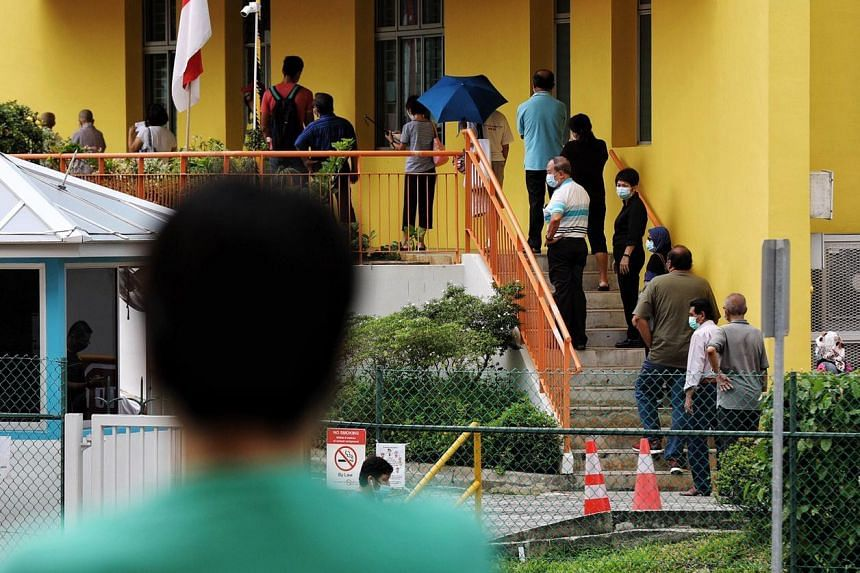 A queue forms outside Changkat Primary School polling station on July 10, 2020.