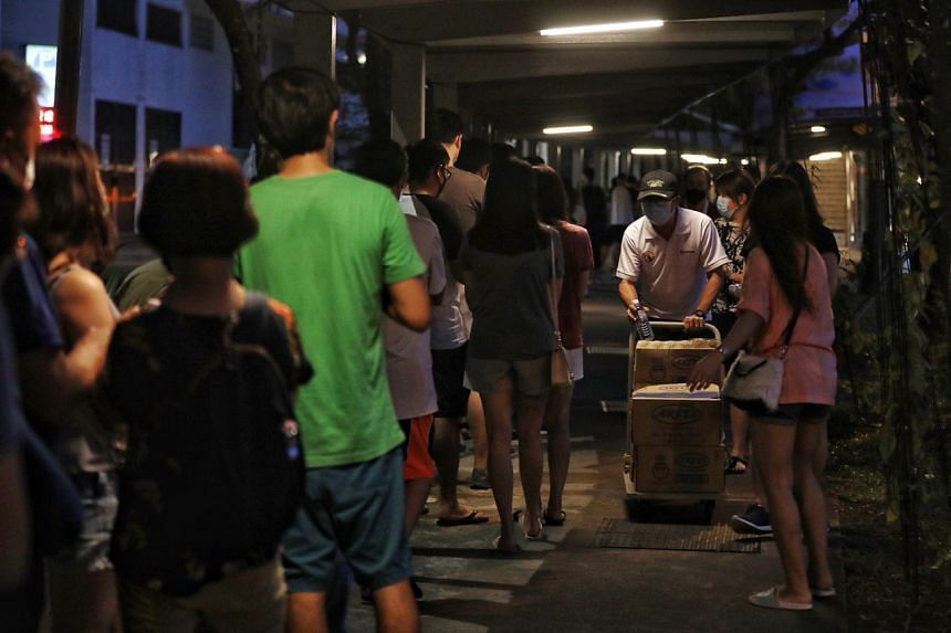 Grassroots leader Gilbert Quek distributing water to voters queueing outside Palm View Primary School on July 10, 2020.