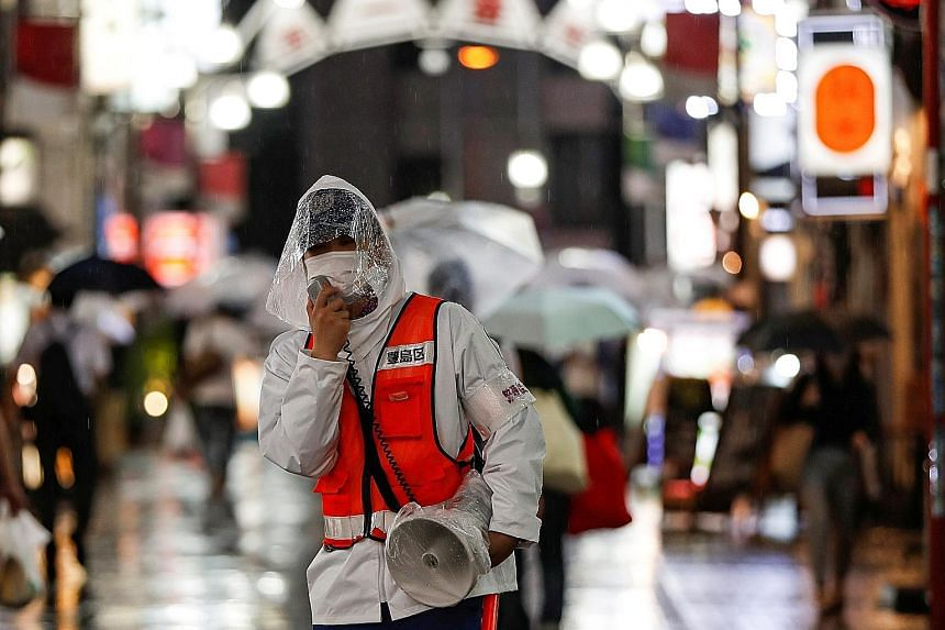 A security person in Tokyo reminding people about measures against the coronavirus. Japan is trying to balance containment efforts with economic revival. PHOTO: REUTERS