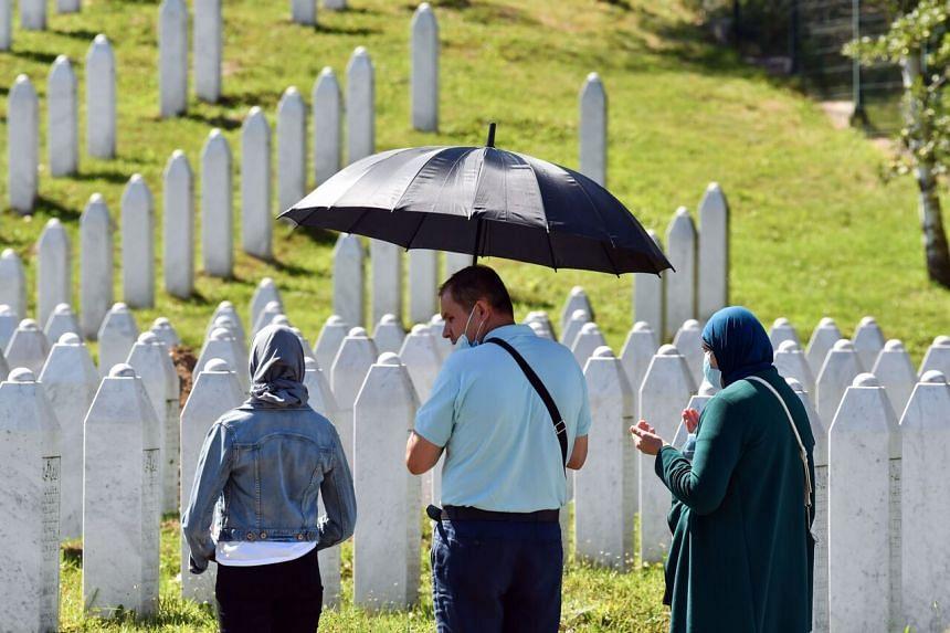 Bosnian Muslim family pray near graves of their relatives in Srebrenica, on July 10, 2020.