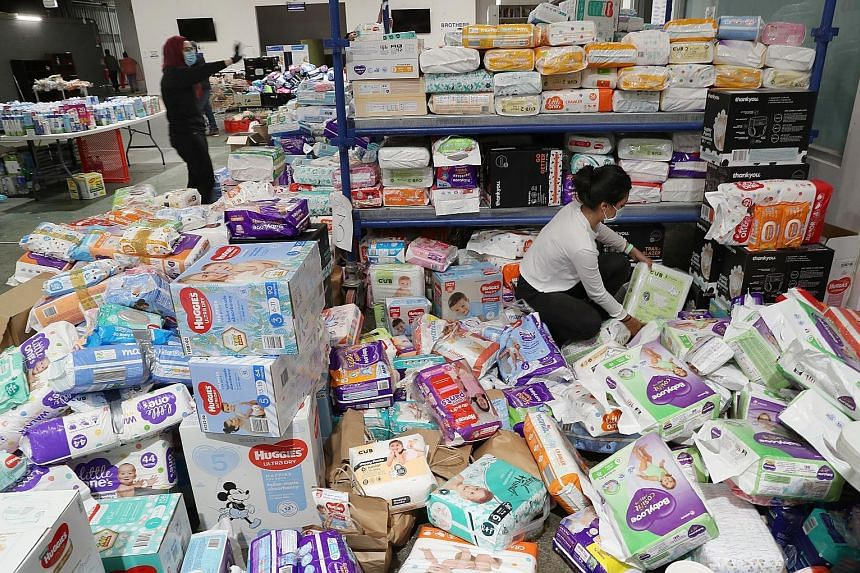 Volunteers in Melbourne, Victoria, sorting out donated supplies for residents of the Alfred Street public housing tower, which remains under tight lockdown due to the coronavirus pandemic. Victoria reported 216 new coronavirus cases yesterday. PHOTO: