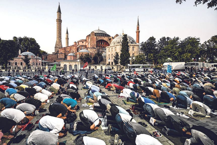 People praying outside the Hagia Sophia in Istanbul on Friday. The monument was constructed as a cathedral, converted into a mosque and later preserved as a museum, but its status as a museum has since been revoked. PHOTO: AGENCE FRANCE-PRESSE