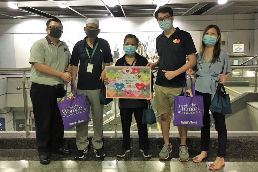 Be Kind SG founder Sherry Soon (far right) and volunteer Matthew Kong (beside her) with MRT station staff and cleaners at Clarke Quay MRT station on July 11, 2020.