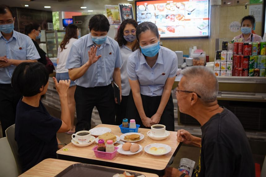 The Workers' Party team consisting (from left) Louis Chua, Jamus Lim, Raeesah Khan and He Ting Ru speak to residents during a small thank you walkabout at Rivervale Plaza on July 12, 2020.