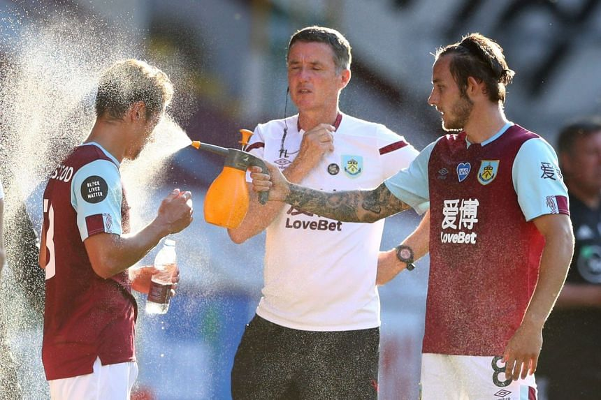 Burnley's Josh Brownhill spraying water on Ashley Westwood during a drinks break, one of the protocols for the Premier League restart.