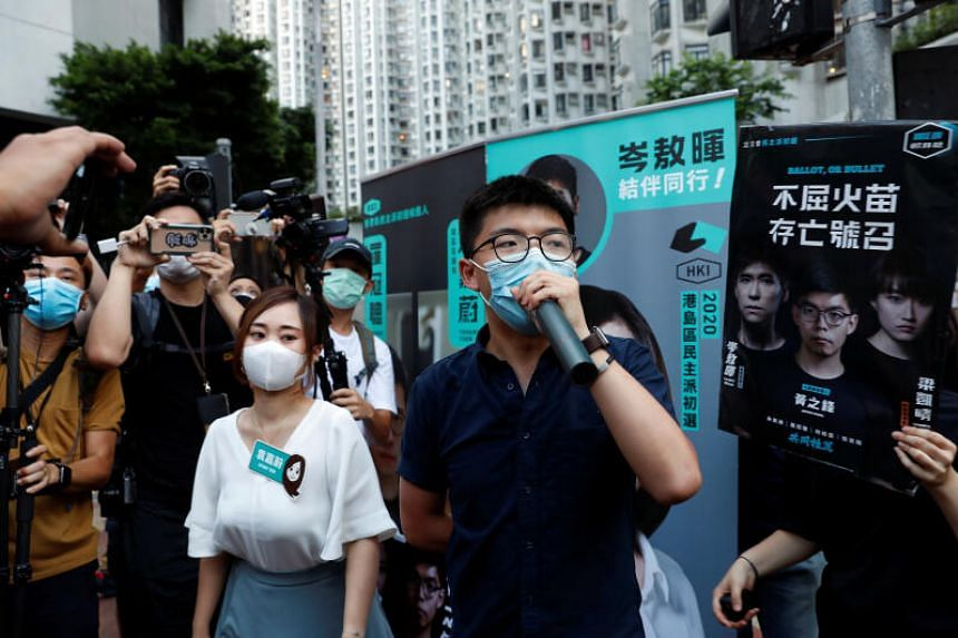 Pro-democracy activists Tiffany Yuen Ka-wai (left) and Joshua Wong attend a campaigning during primary elections, in Hong Kong, on July 11, 2020.