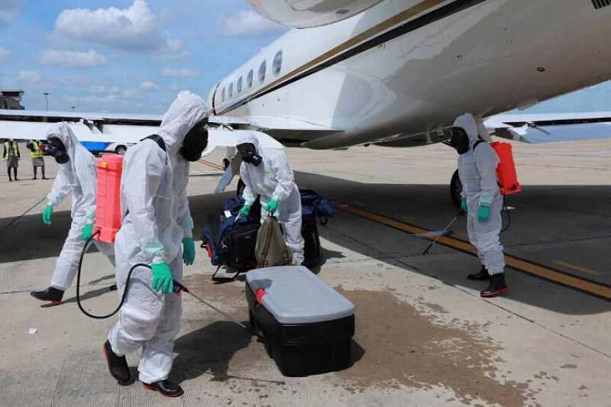 Health officers spray disinfectant on luggage at a military airport in Bangkok, on July 9, 2020.