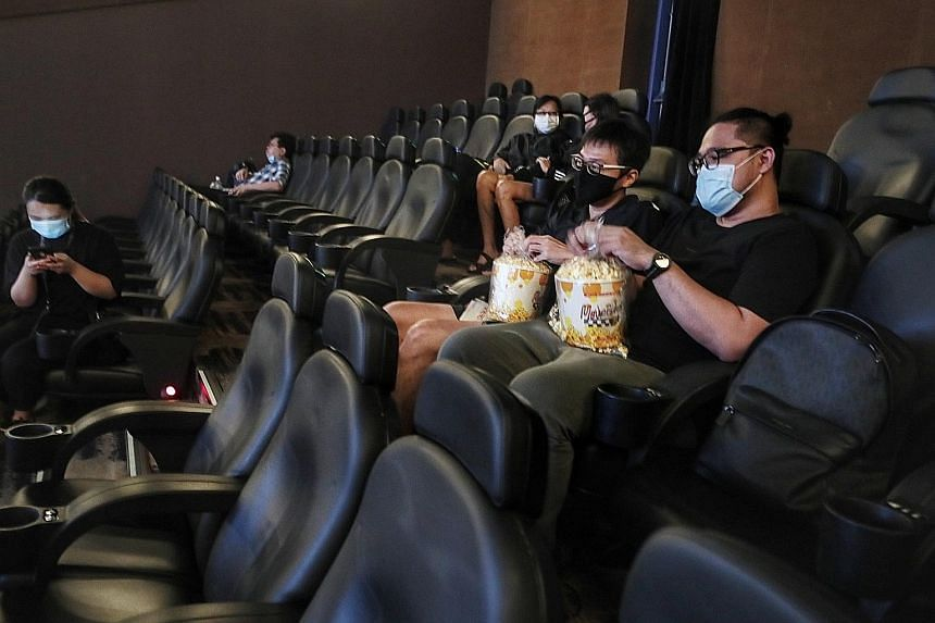 Above: Mr Thomas Chih (left) and his friend, who wanted to be known only as Mr Cortez, 36, having popcorn at the 9.50am screening of biographical drama Escape To Pretoria at Shaw Theatres Nex yesterday. ST PHOTO: KELVIN CHNG Left: (From right) Movieg