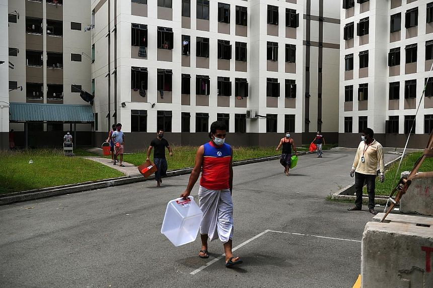 Residents of Tampines Dormitory heading to the food collection centre to pick up their lunch early last month. Many workers staying in dormitories who are infected are likely to show no symptoms, allowing the virus to continue spreading and making th