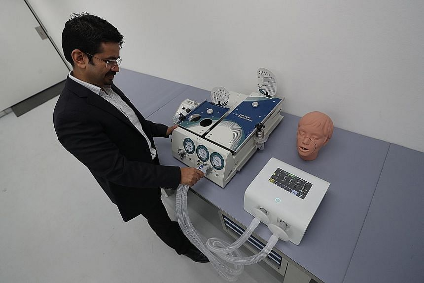 Above: ABM Respiratory Care's chief executive Vinay Joshi with the Alpha ventilator at Advanced MedTech's Tuas facility. The ventilator is converted from ABM Respiratory Care's FDA-approved respiratory device. Left: Advanced MedTech's technicians and