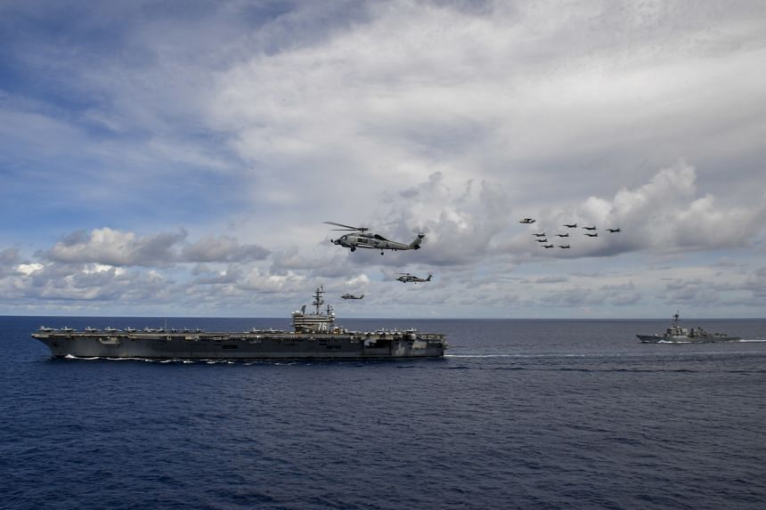 Aircraft fly in formation near the aircraft carrier USS Ronald Reagan, in the South China Sea, on July 5, 2020.