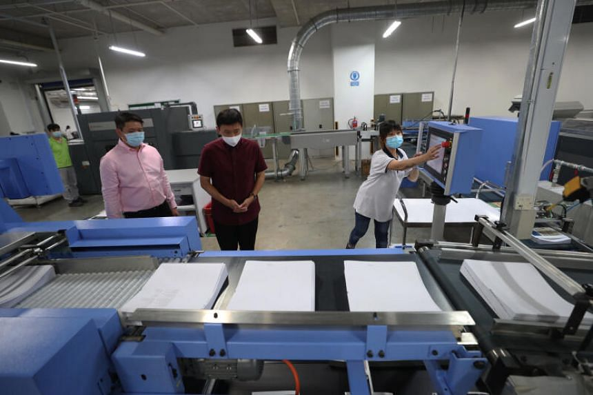Senior Minister of State for Trade and Industry Chee Hong Tat (centre) touring Markono Content Solutions' printing facility.