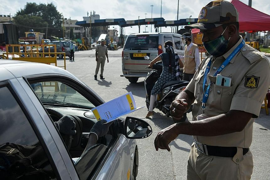 A policeman at the Karnataka-Tamil Nadu state border checkpost on the outskirts of Bangalore directing people in a car from neighbouring Tamil Nadu to undergo health screening on Monday. The Indian city of Bangalore, which saw over 1,300 Covid-19 cas