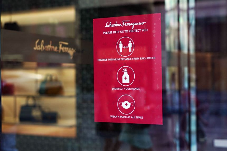 A sign describing safety precautions is displayed in the window of a Salvatore Ferragamo store in New York City.