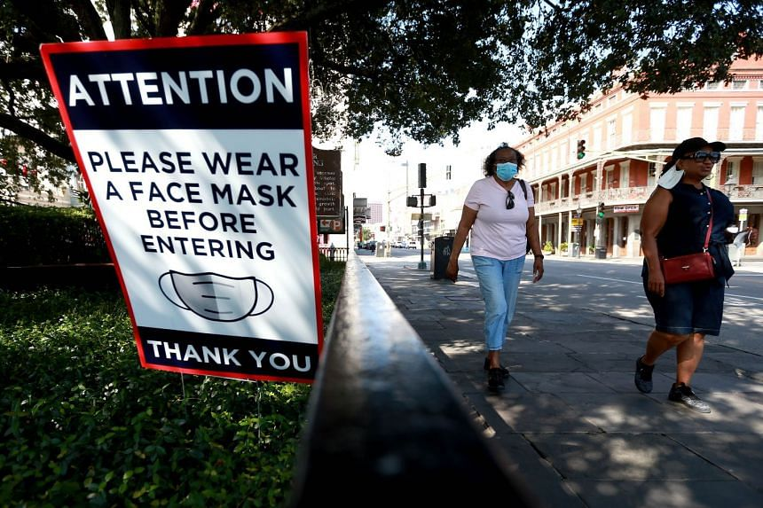 Visitors walk past face mask signs in the French Quarter of New Orleans, Louisiana.