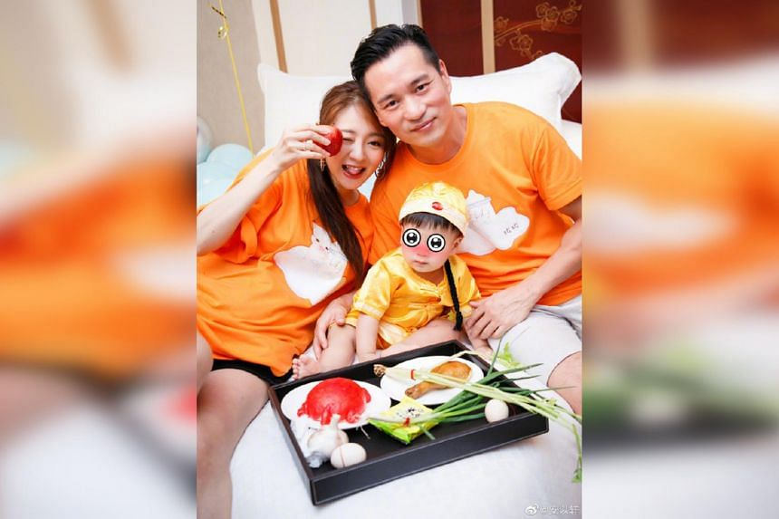 Ady An (left) celebrates the one-year-old birthday of her son with her husband Levo Chan (right).