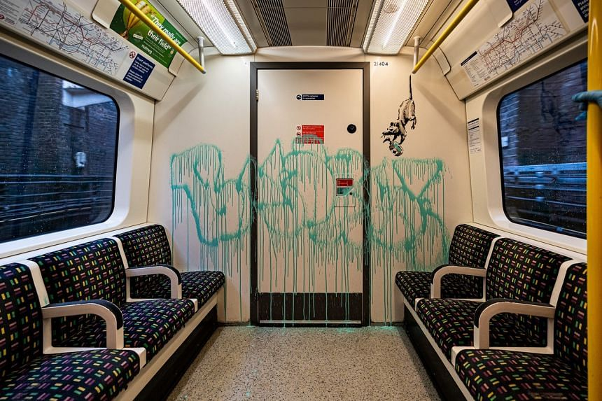An artwork by Banksy is seen on a London underground train carriage.