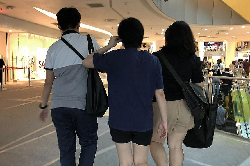 Retrenched staff from Resorts World Sentosa (RWS) carrying black bags containing a folder with their employment details and testimonials at VivoCity mall yesterday. RWS declined to specify how many staff were laid off.