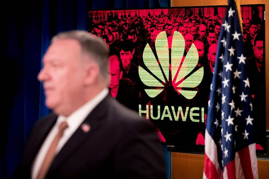 A monitor displays the logo for Huawei behind Pompeo as he speaks in Washington.
