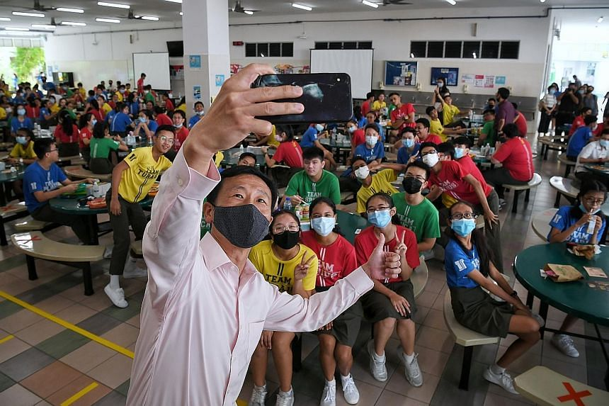 Right: A teacher conducting a character and citizenship education class with Secondary 3 students at Tampines Secondary School. Far right: Education Minister Ong Ye Kung taking a wefie with Secondary 4 students at Tampines Secondary yesterday. Mr Ong