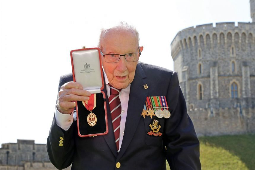 Tom Moore poses with his medal after being made a Knight Bachelor during an investiture at Windsor Castle.