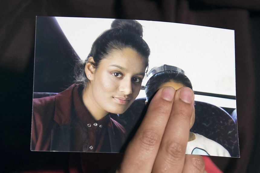 A 2015 photo shows Shamima Begum's sister holding a picture of Shamima during an interview in London.
