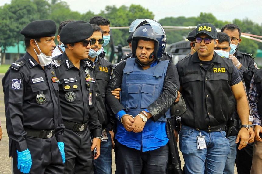 Rapid Action Battalion personnel escort Mohammad Shahed (centre) allegedly accused of distributing fake Covid-19 certificates, following his arrest, in Dhaka, on July 15, 2020.