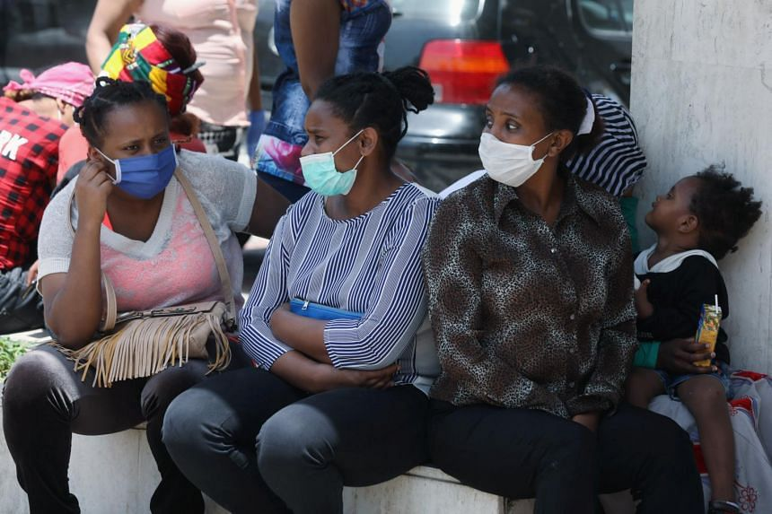 Ethiopian domestic workers wearing sit in front of the Ethiopian consulate in Lebanon.