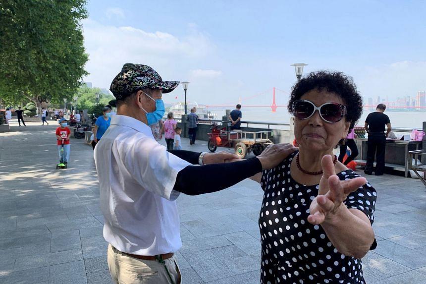People dance by the Yangtze river in Wuhan, in June 2020.