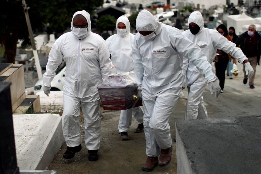 Workers carry the coffin of a 62-year-old coronavirus victim near Rio de Janeiro, Brazil, July 16, 2020.